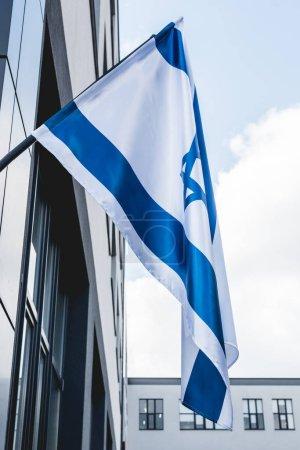 Photo pour Vue de bas angle du drapeau israélien national près de la construction - image libre de droit