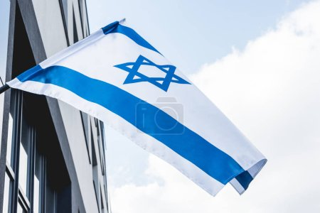 low angle view of national israel flag with star of david near building against blue sky