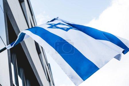 Photo pour Vue de bas angle du drapeau d'Israël avec l'étoile de David près de la construction contre le ciel - image libre de droit