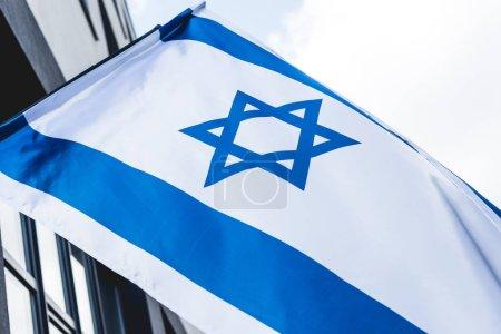 Photo pour Vue de bas angle du drapeau national d'Israël avec l'étoile de David près de la construction contre le ciel - image libre de droit