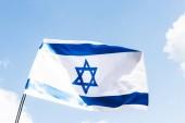 """Постер, картина, фотообои """"низкий угол зрения национального флага Израиля с синей звездой Давида против неба"""""""