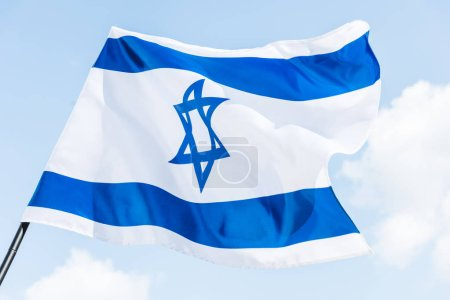 low angle view of national israel flag with star of david against blue sky