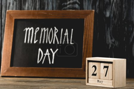 Photo for Cubes with date near chalkboard with memorial day lettering on wooden surface - Royalty Free Image