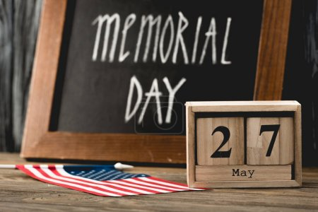 Photo pour Cubes en bois avec date près du drapeau de l'Amérique avec des étoiles et des rayures et le jour de Memorial lettrage sur le tableau noir - image libre de droit