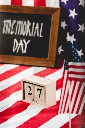 Foto de Cubos con fecha cerca de la bandera de América con estrellas y rayas y el día de conmemoración de las letras en la pizarra - Imagen libre de derechos
