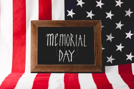 chalkboard with memorial day letters near national flag of america