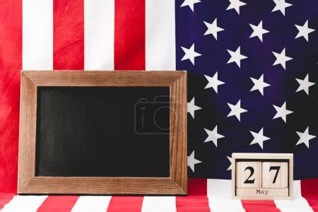 Photo for Empty black board near american flag and wooden cubes with date - Royalty Free Image