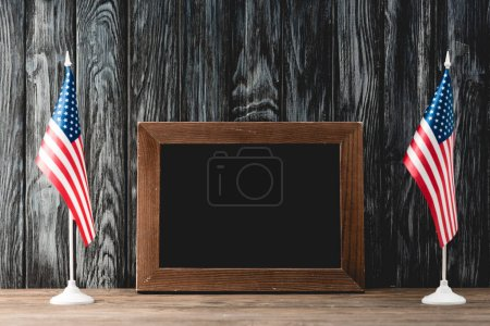 Photo for Empty black board near american flags with stars and stripes - Royalty Free Image