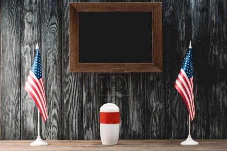 Photo for Empty chalkboard near funeral urn with ashes and flags of america - Royalty Free Image
