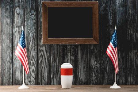 Photo pour Tableau vide près de l'urne funéraire avec des cendres et des drapeaux de l'Amérique - image libre de droit