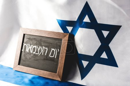 chalkboard with hebrew lettering near national flag of israel