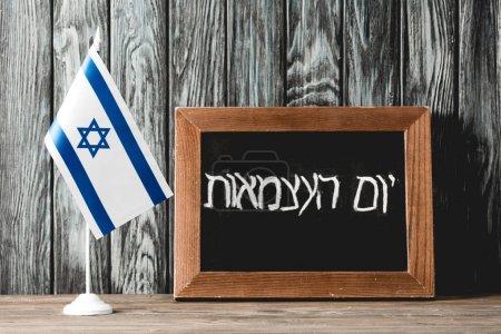 Photo pour Tableau noir avec lettrage hébreu près du drapeau national d'Israël avec étoile bleue de David - image libre de droit