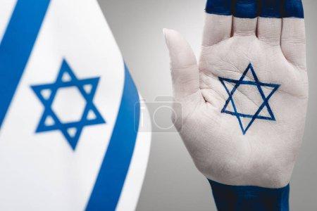 Photo pour Foyer sélectif de la main féminine avec étoile de David près du drapeau sur gris - image libre de droit