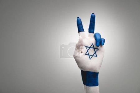 Photo pour Vue recadrée de la main femelle avec étoile de David montrant signe de paix sur le gris - image libre de droit