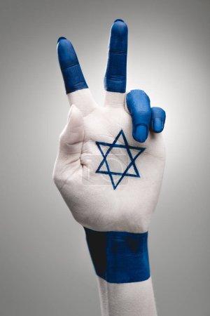 Photo pour Vue recadrée de la main femelle avec étoile bleue de David montrant signe de paix sur le gris - image libre de droit