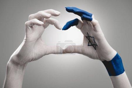 Foto de Vista recortada de manos femeninas con estrella azul de David mostrando el corazón en gris - Imagen libre de derechos