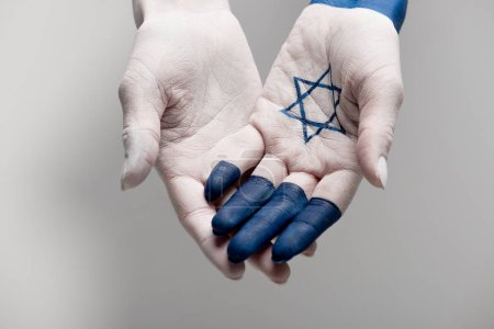 cropped view of hands with blue star of david on grey