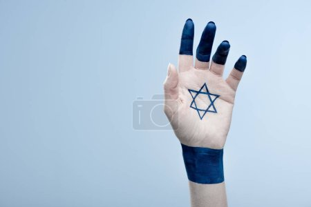 cropped view of female hand with national star of david isolated on blue