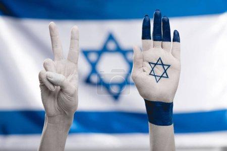 Photo pour Vue recadrée des mains féminines avec étoile de David montrant signe de paix près du drapeau - image libre de droit