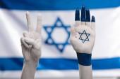 """Постер, картина, фотообои """"обрезанный вид женских рук со звездой Давида показаны знак мира возле флага"""""""