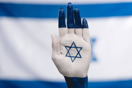 cropped view of female hand with star of david near flag