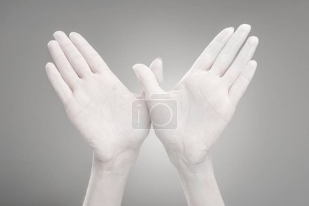 Photo for Cropped view of female hands painted in white showing bird-shape sign on grey - Royalty Free Image