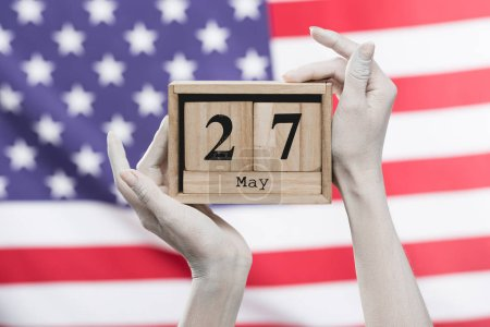 Photo pour Vue recadrée des mains femelles peintes en cubes en bois blanc retenant avec la date près du drapeau américain - image libre de droit