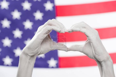 Photo for Cropped view of female hands painted in white showing heard-shaped sign near american flag - Royalty Free Image