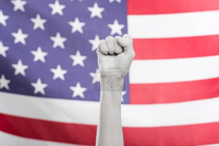 Photo for Cropped view of female hand painted in white showing fist near american flag - Royalty Free Image