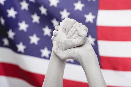 Photo pour Vue recadrée des mains serrées féminines peintes en blanc près du drapeau américain - image libre de droit