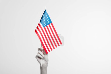cropped view of female hand painted in white holding american flag isolated on grey
