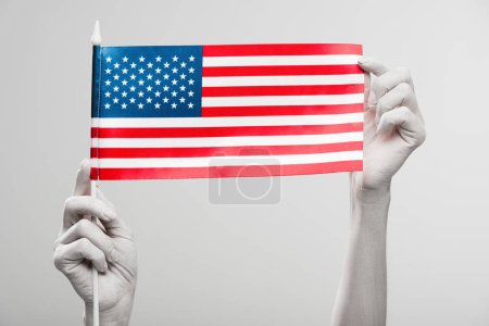 cropped view of female hands painted in white holding american flag isolated on grey
