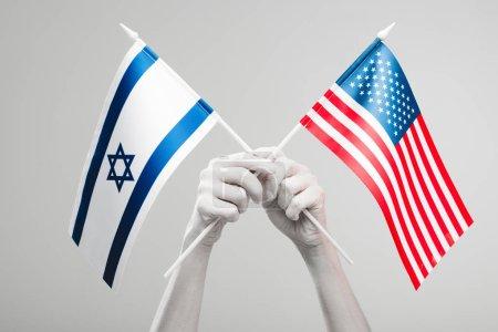 Photo pour Vue recadrée des mains féminines peintes en blanc tenant croisé américain et Israël drapeaux isolés sur le gris - image libre de droit