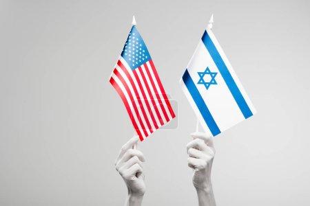 Photo pour Vue recadrée des mains féminines peintes en blanc retenant les drapeaux américains et israéliens isolés sur le gris - image libre de droit