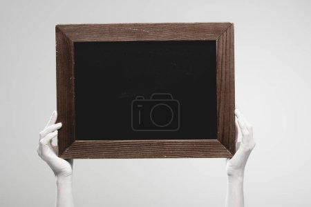 Photo for Cropped view of female hands painted in white holding empty chalkboard isolated on grey - Royalty Free Image