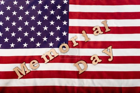 Photo for Top view of memorial day lettering on american flag with stars and stripes - Royalty Free Image