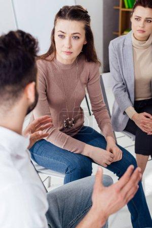 femmes et hommes assis et discutant pendant la séance de thérapie de groupe