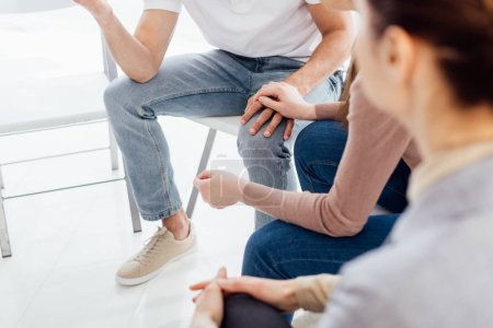Photo for Partial view of people sitting and holding hands during group therapy session - Royalty Free Image