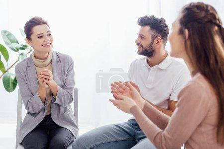 Photo pour Sourire les femmes et les hommes assis et applaudissant au cours de la session de thérapie de groupe - image libre de droit
