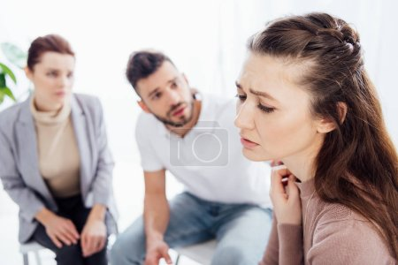 selective focus of worried woman during group therapy session