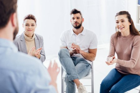 Photo for Selective focus of people applauding while looking at man during group therapy session - Royalty Free Image