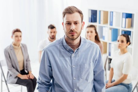 Photo for Man looking at camera while people sitting during group therapy session - Royalty Free Image
