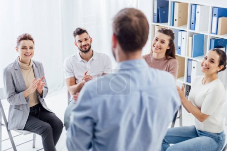 Photo for Smiling people applauding while looking at man during group therapy session - Royalty Free Image