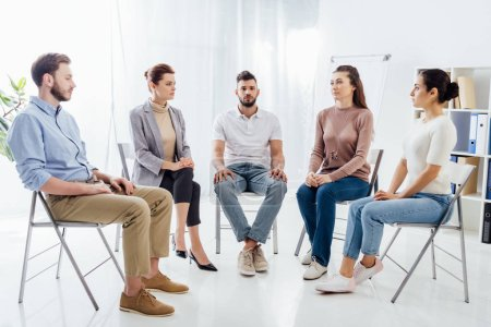 Photo for People in casual clothes sitting on chairs during support group session - Royalty Free Image