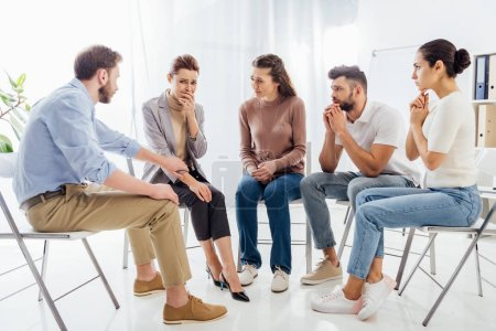 people sitting on chairs and having group therapy meeting