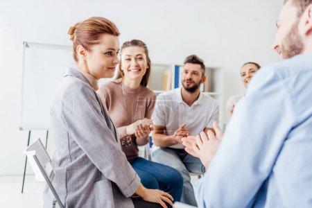Photo pour Des gens souriants assis et applaudissant lors d'une réunion de thérapie de groupe - image libre de droit