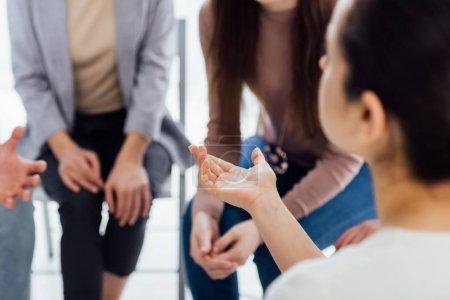 Photo pour Vue arrière du femme gesticulant avec la main au cours de la séance de thérapie de groupe avec espace copie - image libre de droit