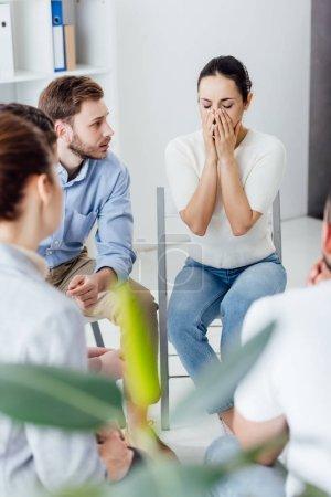 Photo pour Foyer sélectif de la femme couvrant le visage et pleurant pendant la réunion de thérapie de groupe - image libre de droit