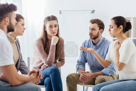 Photo pour Personnes assises sur des chaises et discutant pendant la réunion du groupe de soutien - image libre de droit