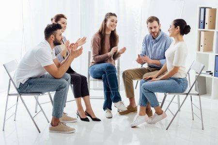 Photo pour Groupe de gens assis sur des chaises et à applaudir au cours de la séance de thérapie - image libre de droit